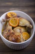 Stock Photo of Grilled chicken with orange slices in casserole dish, studio shot