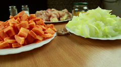 Carrot, onion, garlic and meat - ingredients for rice pilaf. dolly shot. Stock Footage