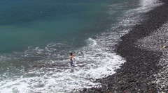 Little boy bathing in the sea, stony beach, Madeira, Portugal Stock Footage