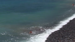 The people bathing in the sea, stony beach, Madeira, Portugal Stock Footage