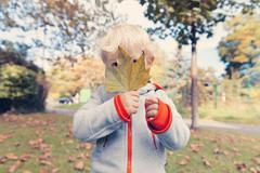 Stock Photo of Germany, Bonn, Baby boy covering face with  autumnal leaf i