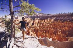 Stock Photo of USA, Utah, young female tourist looking down to the Hoodoo rock formations in