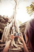 Cambodia, Angkor Wat, Woman takes pictures of the famous tree in Ta Prohm Temple Stock Photos