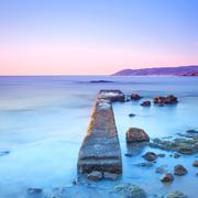 Concrete pier or jetty and rocks on a blue sea. hills on background Stock Photos