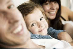 Stock Photo of Young parents with little daughter sitting on sofa at home, close-up