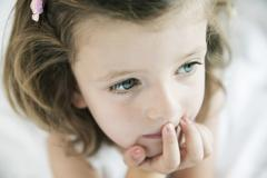 Portrait of thoughtful little girl, close-up Stock Photos