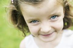Smiling little girl with blue eyes watching at camera Stock Photos