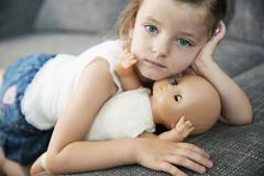 Stock Photo of Portrait of little girl lying on sofa with her doll, close-up