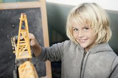 Blond boy playing with toy crane Stock Photos