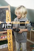 Blond boy playing with toy crane - stock photo