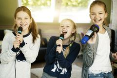 Three girls singing with microphone Stock Photos