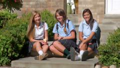 Three Pretty Uniformed Teen School Girls, Sitting & Looking At The Camera Stock Footage