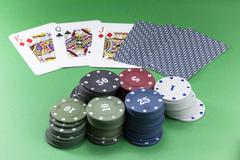 poker chips and cards on felt on green - stock photo