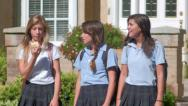 Stock Video Footage of Three Pretty Uniformed Teen School Girls Standing At A Curb