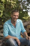 Stock Photo of Germany, Bavaria, Smiling man at woodpile