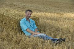 Germany, Bavaria, Man leaning against bale of straw Stock Photos