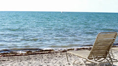 Beach lounge chair on an empty beach in the Florida Keys Stock Footage