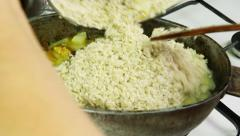 Chief adding rice in kettle with simmering ingredients of pilaf Stock Footage