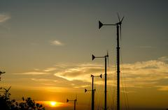 Wind turbines silhouette in the sunset sky Stock Photos