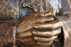 Hands of the statue of a priest who pray Stock Photos