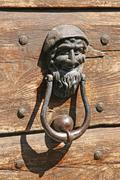 iron door knockers with one face to knock - stock photo
