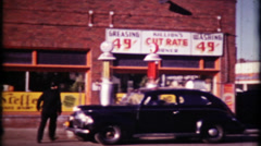 630 - gas station keeps busy on city street - vintage film home movie Stock Footage