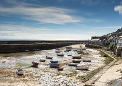 Cornish fishing village of Mousehole with blue sky and clouds at low tide - stock photo