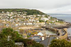 View of Mousehole harbour and fishing village Cornwall on overcast cloudy day - stock photo