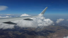 Airplane wing above the clouds and mountains Stock Footage