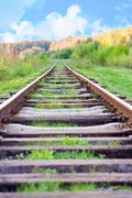 railway tracks in a rural scene with nice blue sky - stock photo
