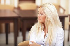 Young beautiful woman sitting in the office and looking aside Stock Photos