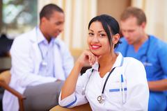 Medical doctor woman smiling indoors with her collegues working behind Stock Photos