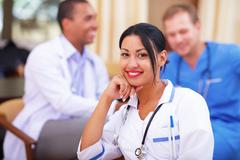Medical latin doctor woman smiling indoors with her collegues working behind Stock Photos
