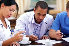 Young african-american doctor making notes at the medical meeting Stock Photos