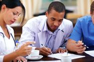 Stock Photo of young african-american doctor making notes at the medical meeting