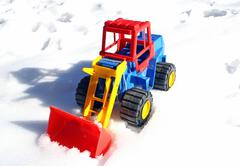 Child's toy scraper in use on fresh snow white Stock Photos