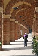 priest walking along the arcades of a cemetery - stock photo