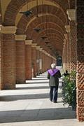 Priest walking along the arcades of a cemetery Stock Photos