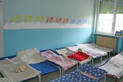 Dormitory for children with small beds and blankets for a kindergarten Stock Photos
