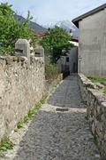 Narrow alleyway paved and stones in the middle of a small villag Stock Photos