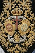 Detail of embroidery on velvet dark green, coat of arms of the brotherhood  Stock Photos