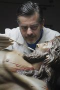 Conservative restoring an image of christ crucified on wood, andalusia, spain Stock Photos
