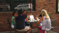 Family dining at outside cafe of Leo's - stock footage
