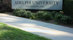 Pedestrian walking by Adelphi University sign (2 of 2) Stock Footage