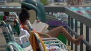 Stock Video Footage of Girl reading at community pool