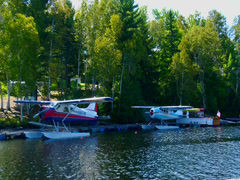 Wide shot of two seaplane docked at a marina Stock Footage
