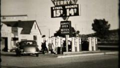 627 - gas station keeps busy on well traveled road - vintage film home movie Stock Footage
