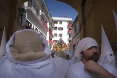 Detail of costaleros and penitents during holy week in the arco del postigo,  Stock Photos
