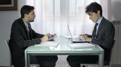 Two business people in elegant suits sitting at desk working in team together Stock Footage