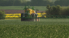 Spraying Pesticides on a corn field in springtime Stock Footage